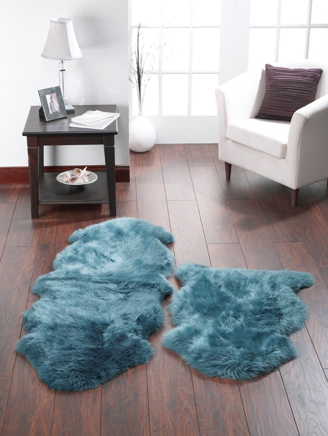 Teal sheepskin rug on wooden floor small living room space