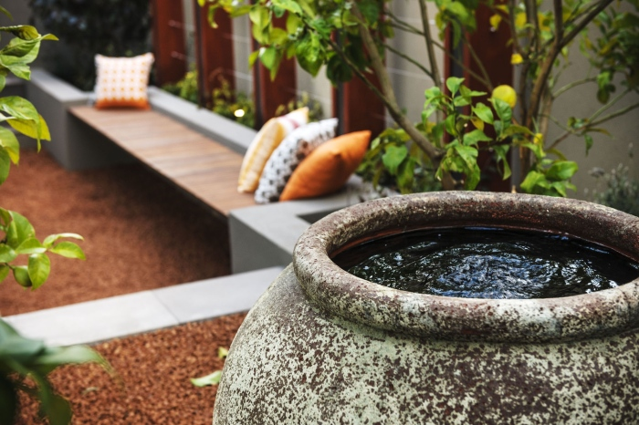 A-garden-area-with-a-big-tattered-pot-filled-with-water