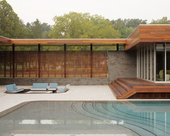 Brick walls on one side with grills of horizontal lines are placed and built near to the swimming pool area
