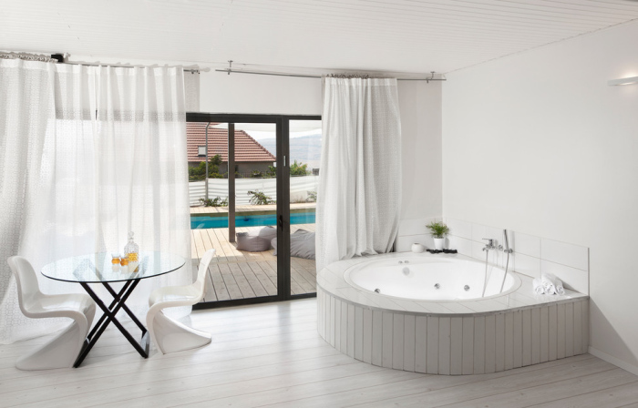 A pool house bathroom with white curtains