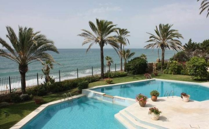 An-exterior-with-two-swimming-pools-nestled-side-by-side-and-a-view-over-the-mediterranian-sea
