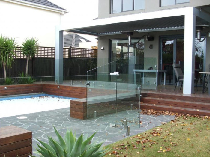 Glass foldable doors with bricks placed all over as a low wall in surrounding the swimming pool
