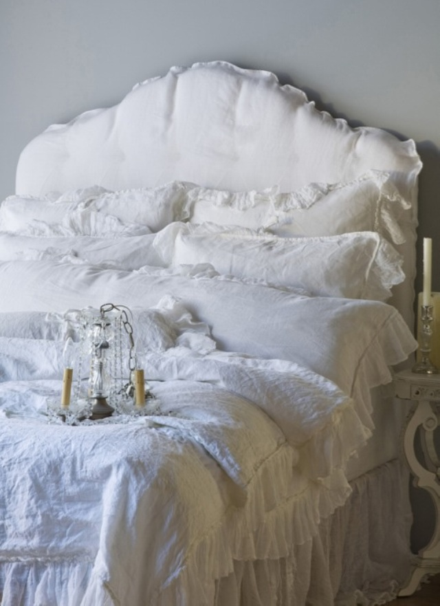 bed stacked with six pillows and all white mattress