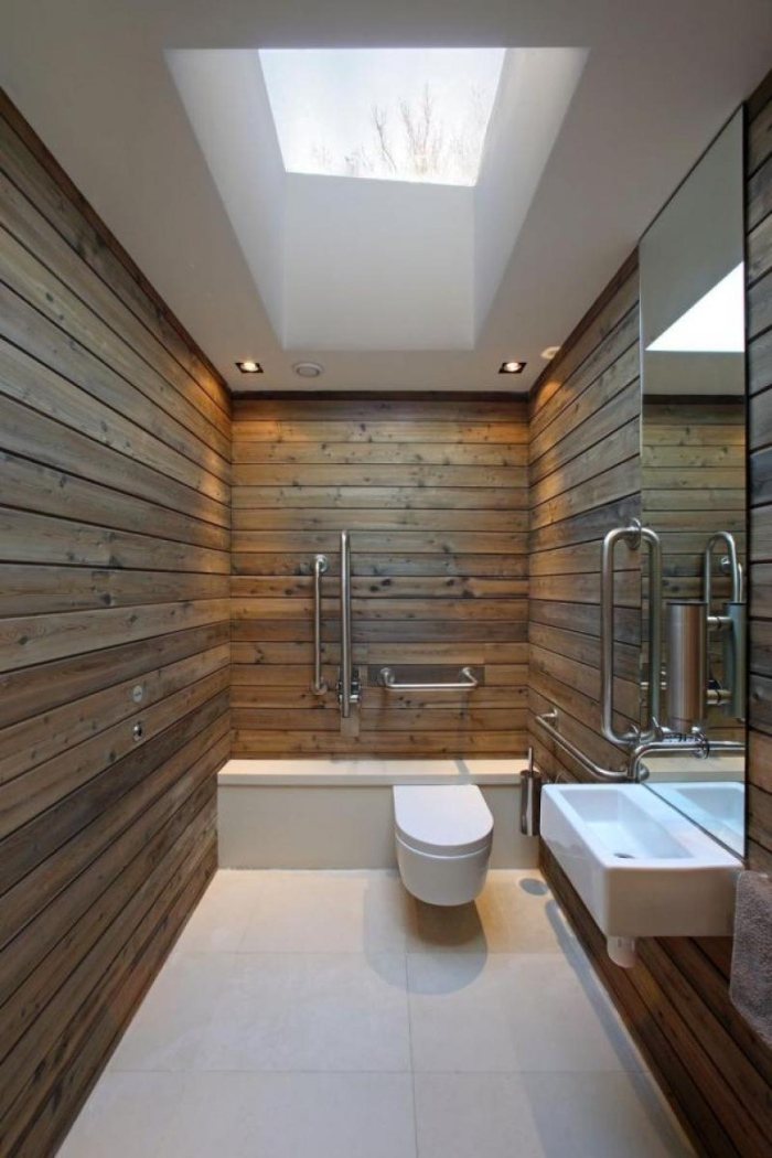 The wooden walls create a balance with white colored tiles, toilet, tub, ceiling, and sink