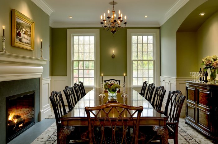 Olive green and white walls create a fusion of colour in the dining room