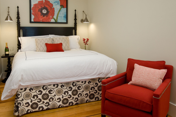 The chair by the bed is upholstered in red and is quite comfortable