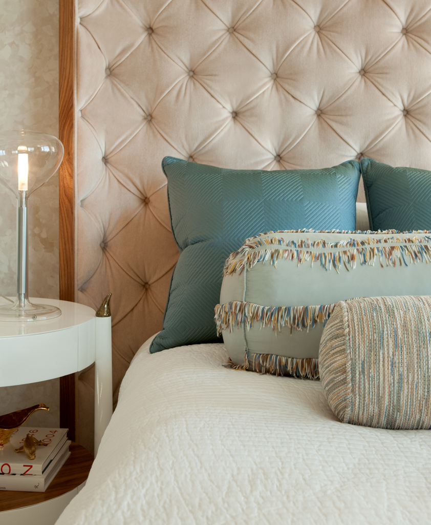 tufted headboard and glass table lamp