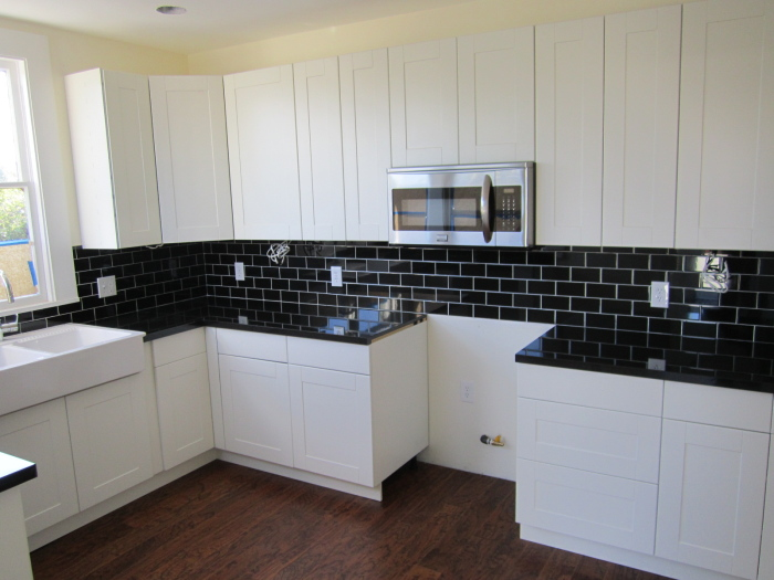 Black subway tiles match with black coloured kitchen counter top