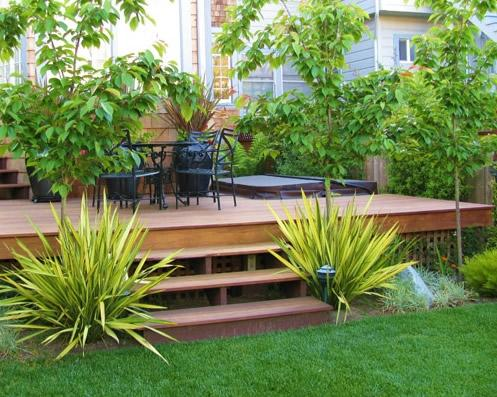 A garden with decking can also be surrounded with trees and tall green plants