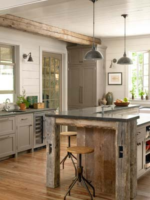 custom island topped with sheet metal echoes barn wood beams in this kitchen
