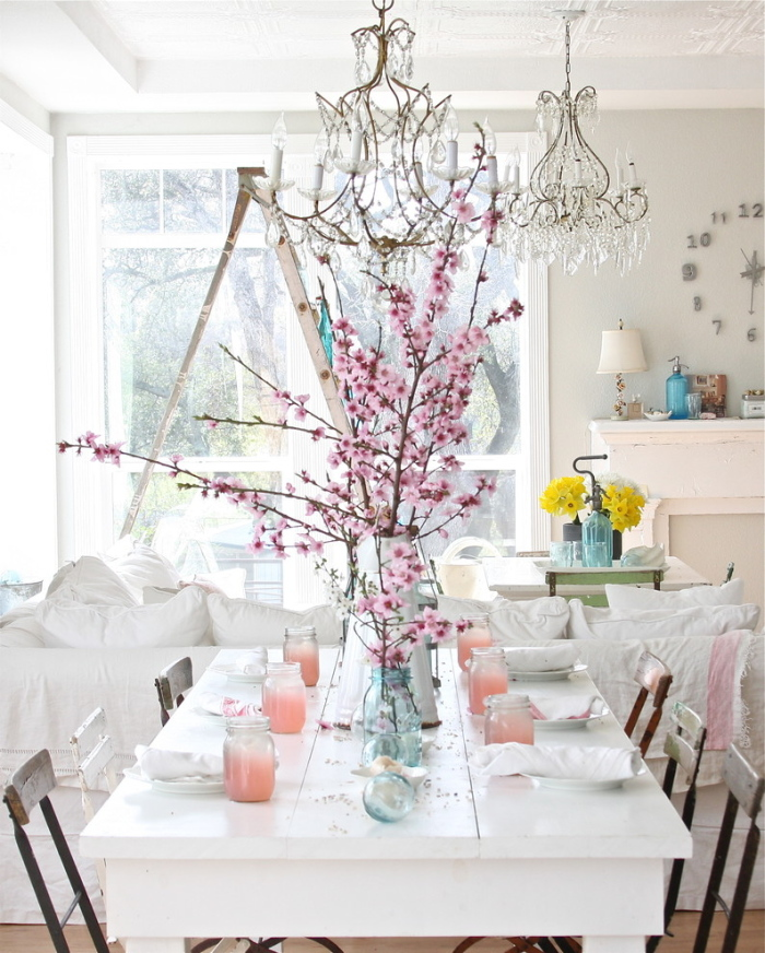 White glazed table with small pink flowers on long twigs