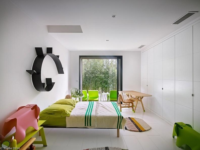 Green colour bed with light wood table is arranged in the room