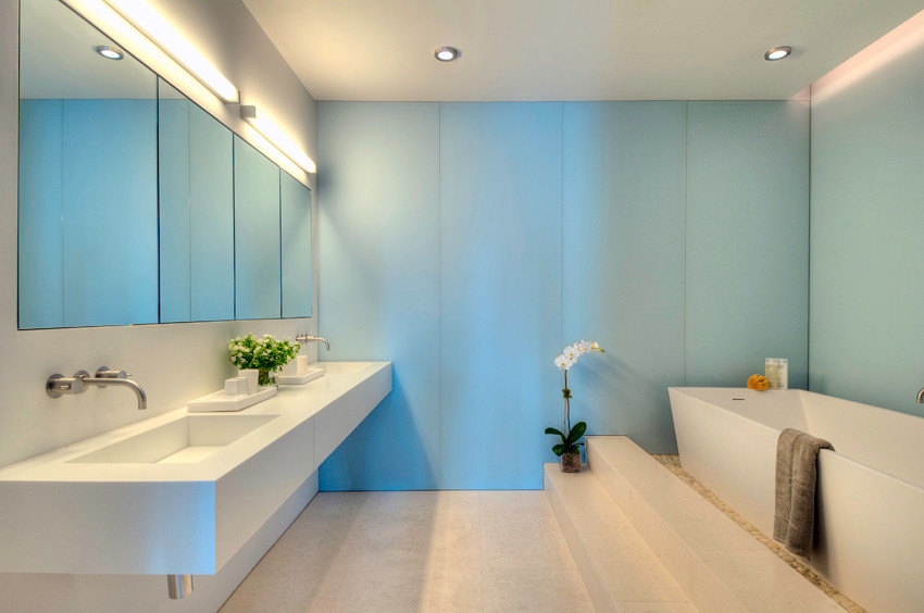 Blue glass adds cool serenity to the minimalist master bathroom
