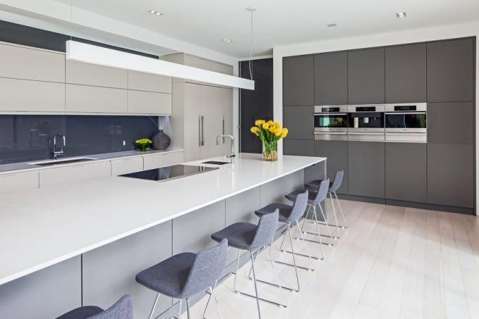 Modern kitchen with the view of the ovens wall cabinets and chairs