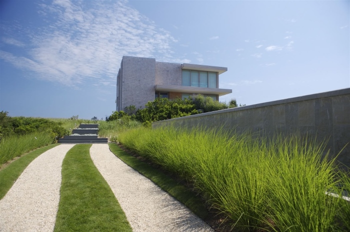 Alternate paths of grass and concrete  leads to the stairs of the house
