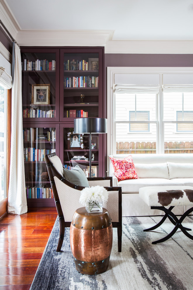Purple book shelf stands out against the whit sofa and drapes used in the room
