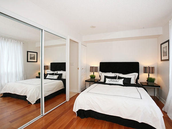Small bedroom with a large mirror