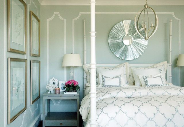 White colour pillar all over the bed with a transparent shiny round mirror