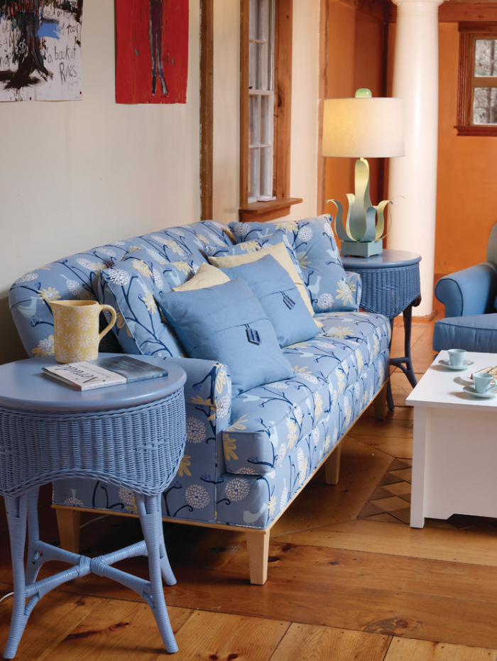 Petite wooden blue sofa looks cozy and inviting