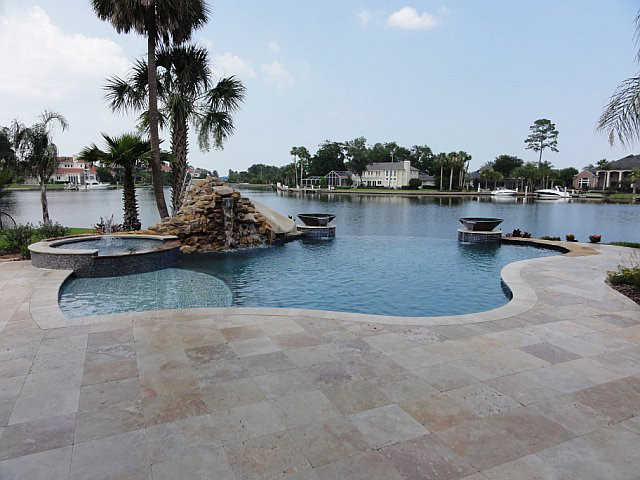 Curvaceous travertine pool decking setup