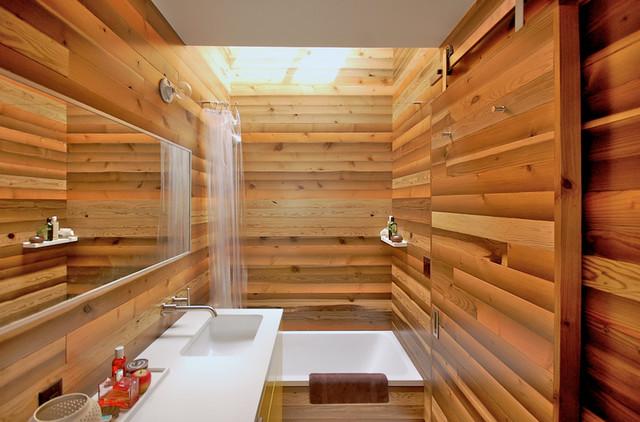 Dark wood wall colour enhances the white tub and sink