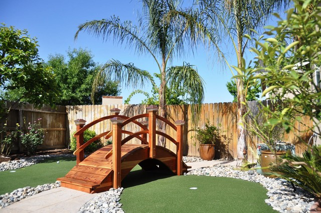 Wooden bridge on the green turf with cobbled stones spread