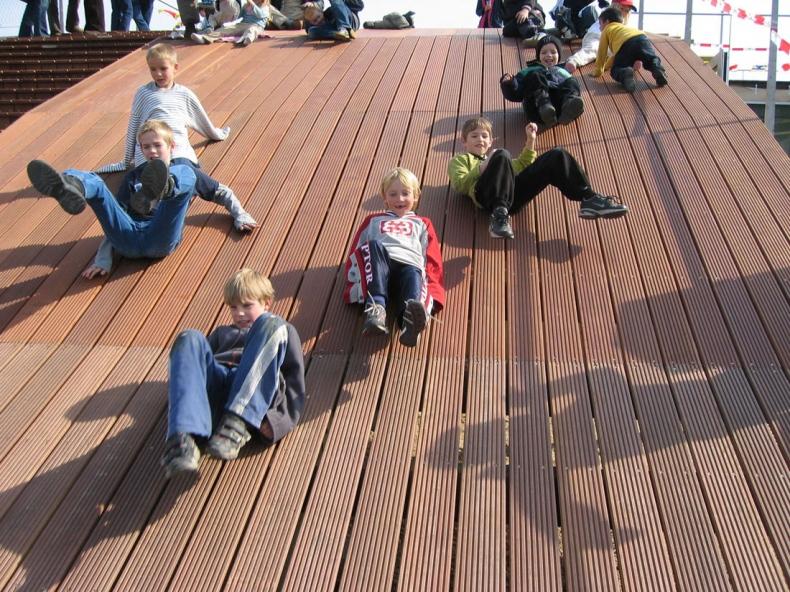 Children slide through the wooden slope