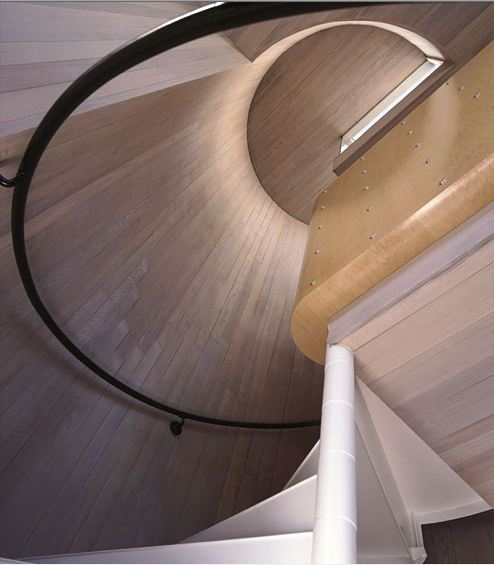 Black railing goes through the stairs in a round manner