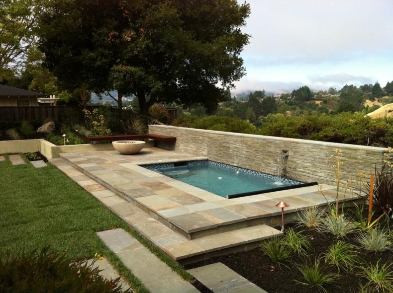 An earthy tub is near the swimming pool