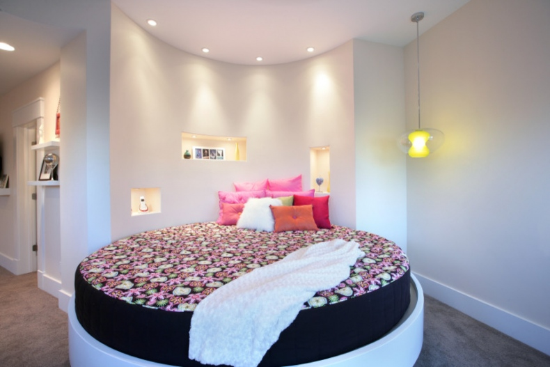 White polished bed with a black velvet round mattress