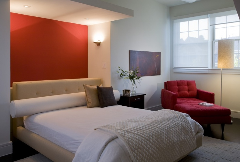 Bedroom with red wall thrown behind the bed