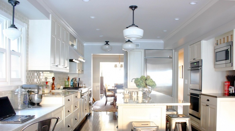 Majestic white culinary space with pendant lights