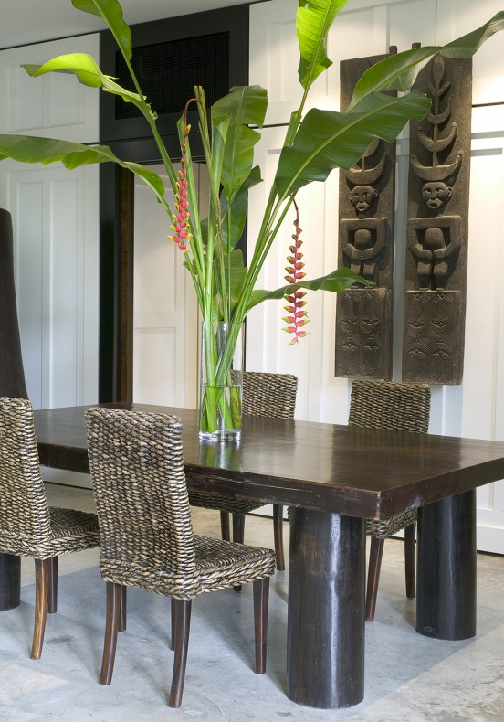 Dining table with teak chairs and big banana leaves in a big glass