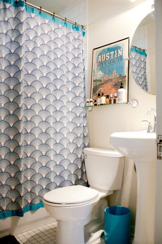 Bedroom with blue waste can and the shower curtain