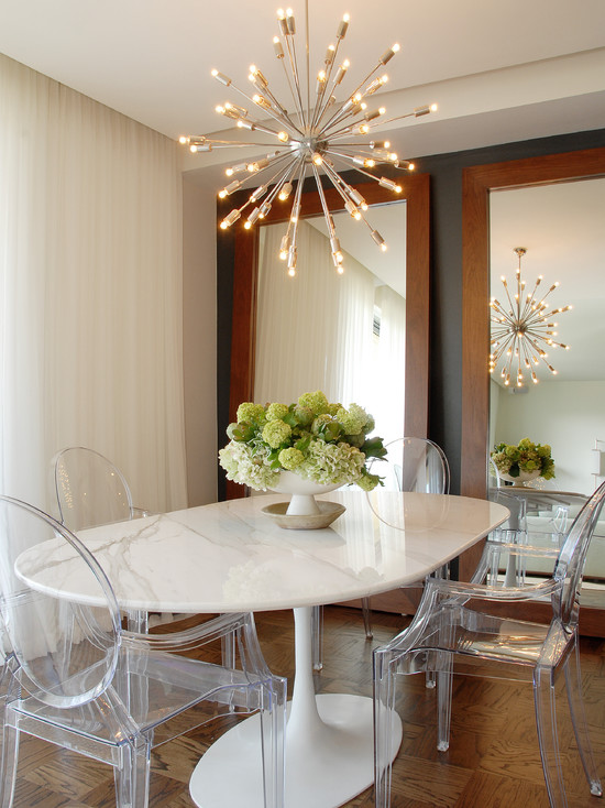 White oval shaped glossy table with transparent chairs besides